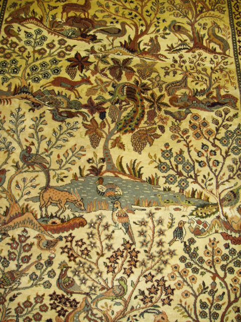 The middle of a decorative Kashmar rug showing a rich garden scene with animals and flowers