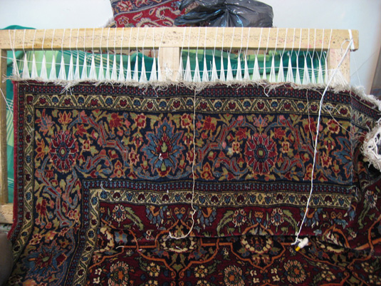 The fringes being lengthened on the Isfahan Rug